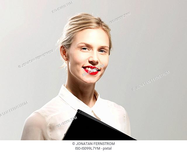 Woman smiling with lipstick stained teeth, studio shot