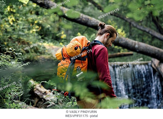 Young hiker with backpack in the forest