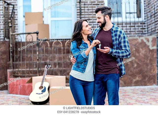 young beautiful couple with keys in front of new house