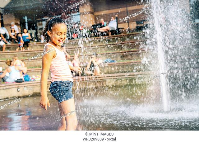 Smiling girl playing in public fountain in summer