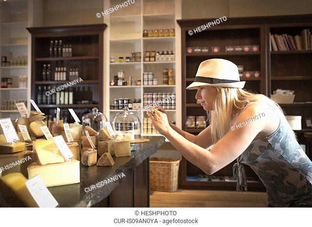 Mid adult woman photographing cheeses on smartphone in organic grocery