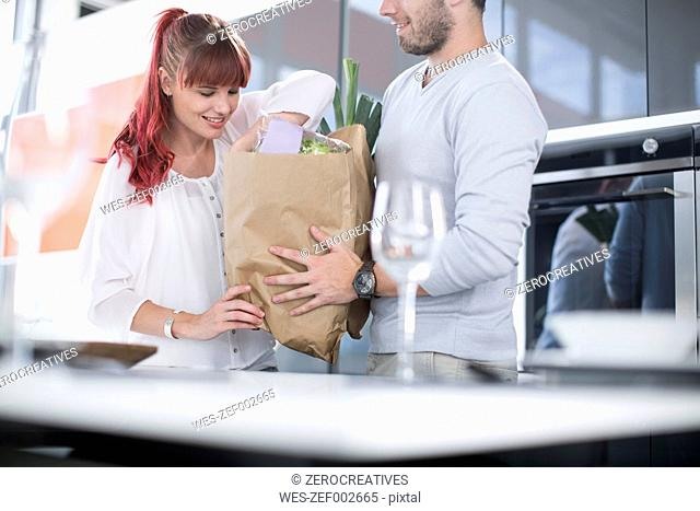 Couple in kitchen unpacking groceries