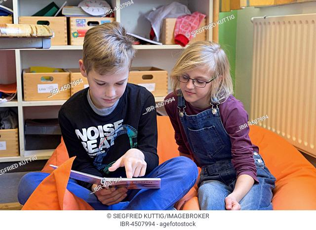 Two students in elementary school reading a book, sitting on beanbag, Lower Saxony, Germany