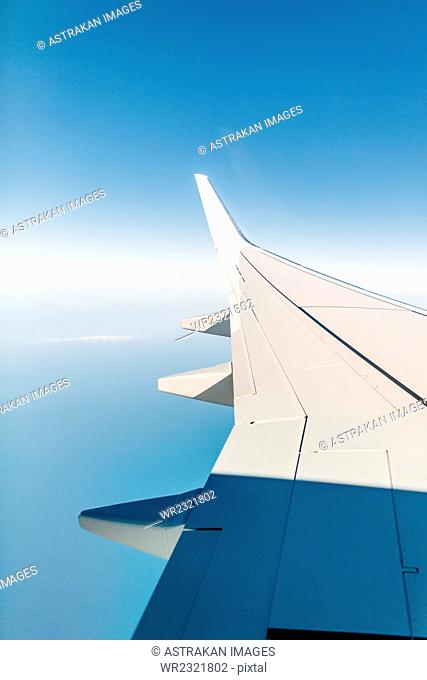 Cropped image of airplane wing against blue sky