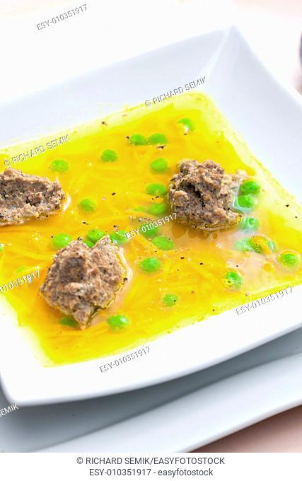 homemade liver dumplings in chicken soup with carrots and peas