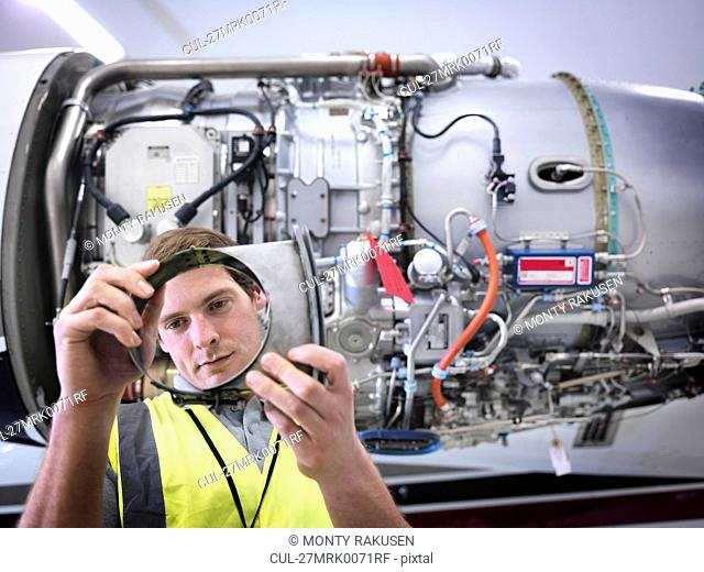 Engineer inspecting part of jet engine