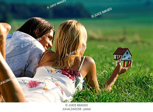 Young couple lying in field daydreaming about owning a house