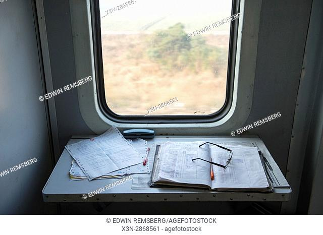 An open notebook, papers, and eyeglasses on a train that is traveling through Ludhiana, India