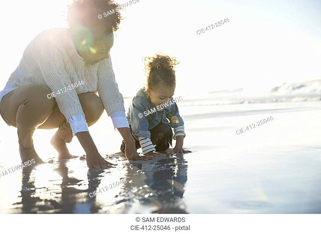 Mother and daughter crouching on beach and touching water