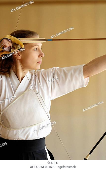 Caucasian woman practicing traditional Kyudo Japanese archery