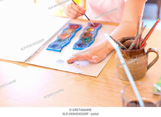 Girl finger-painting with watercolors