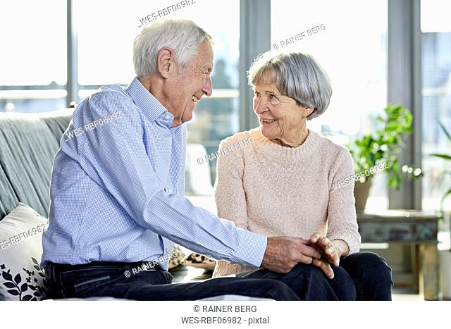 Senior couple sitting on couch talking together