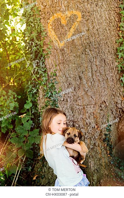 Girl holding puppy dog below tree with heart-shape