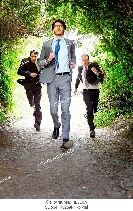 Businessmen running on rural road