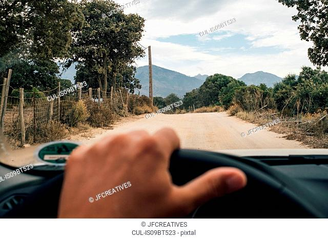 Driver behind wheel of car, road ahead, Calvi, Corse, France