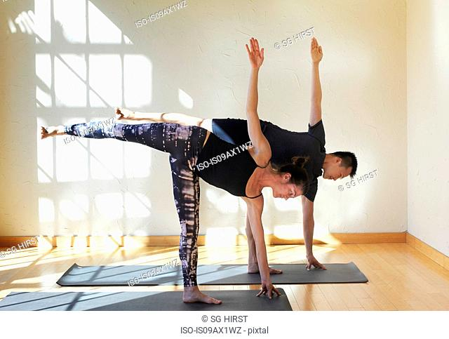 Man and woman doing yoga in studio, in half moon position