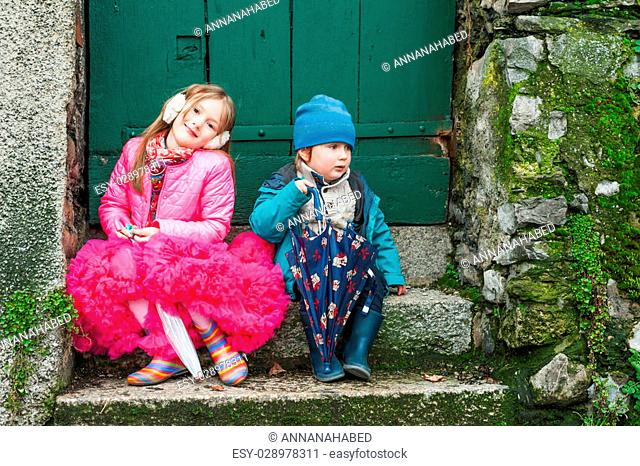 Outdoor portrait of adorable kids, sitting on steps, holding umbrellas