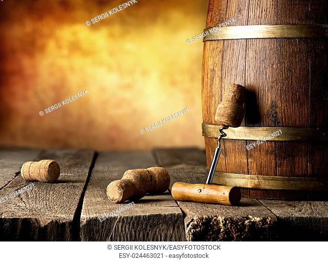Barrel with wine and corkscrew on a wooden table