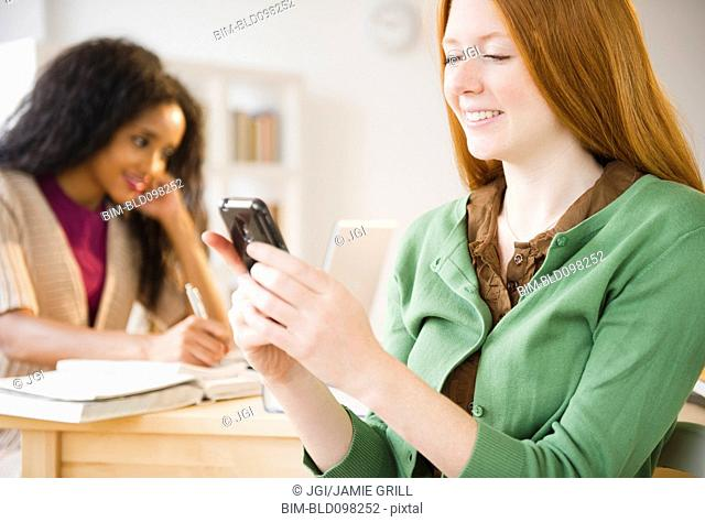 Caucasian woman text messaging on cell phone