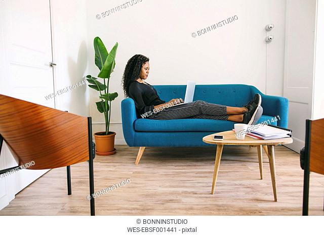 Businesswoman sitting on couch in office using laptop