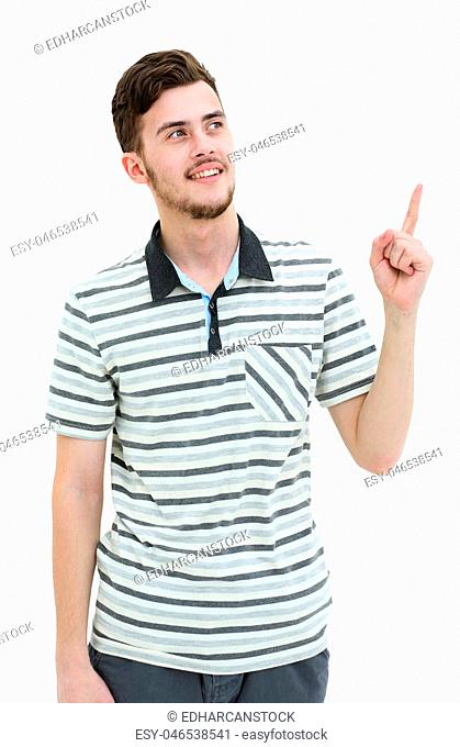 Young man pointing at something with his finger isolated on white