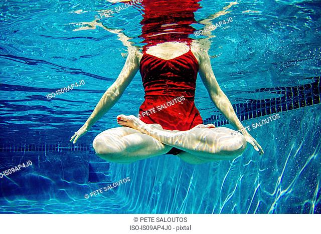 Mature woman wearing red dress, legs crossed, underwater view, low section