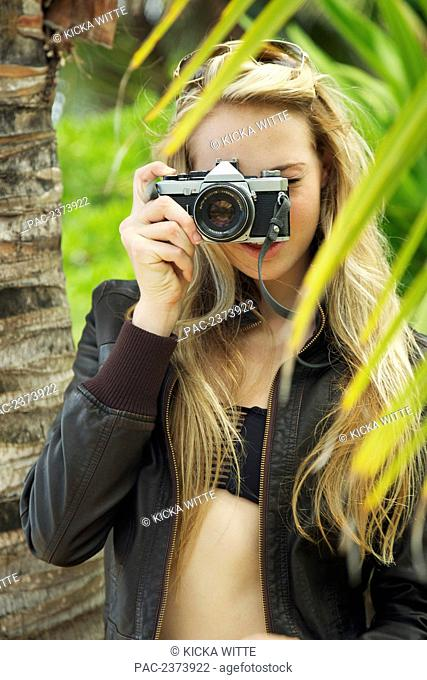 A young woman looking through the camera at the camera; Kauai, Hawaii, United States of America