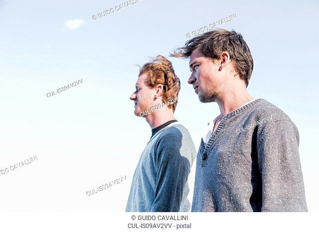 Low angle side view of young men looking away, Costa Smeralda, Sardinia, Italy