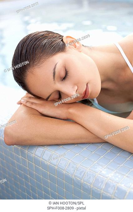 MODEL RELEASED. Woman relaxing in a pool