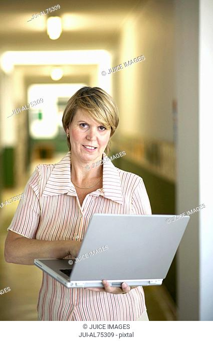 View of a middle-aged woman standing while using a laptop