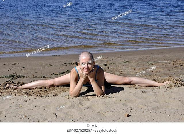 Bald woman sitting in split leaning on her elbows on a sandy river beach, smiling