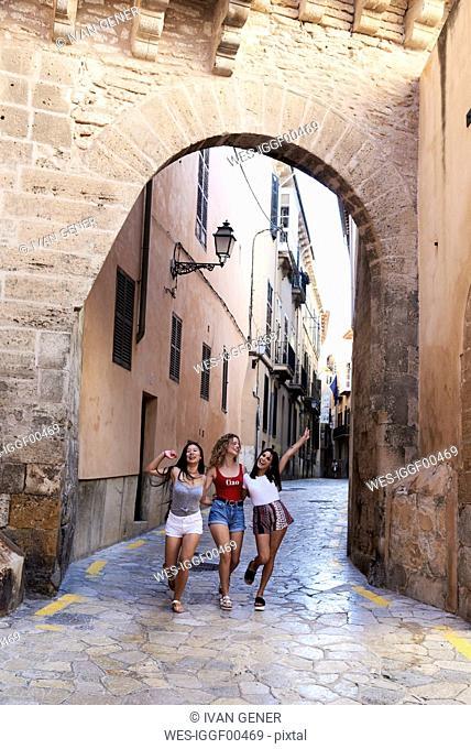 Spain, Mallorca, Palma, three happy young women exploring the city
