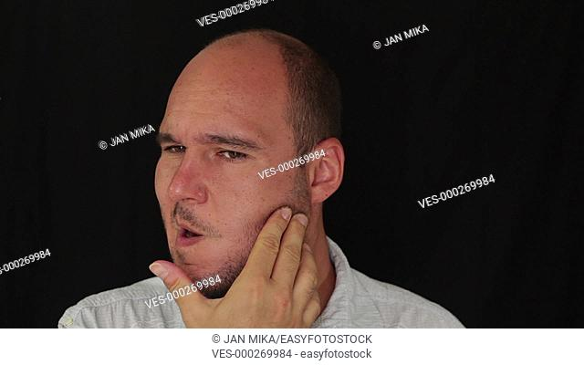 Unhappy man with toothache touching his face