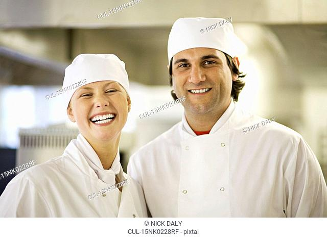 Two chefs in a kitchen smiling