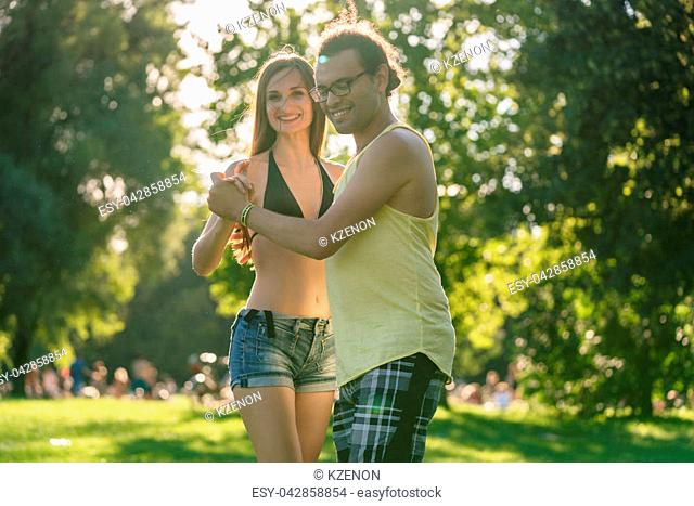 Mann turning woman while dancing Bachata in the sun in park