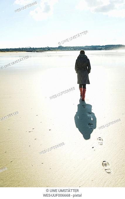 France, Bretagne, Finistere, Crozon peninsula, woman walking on the beach