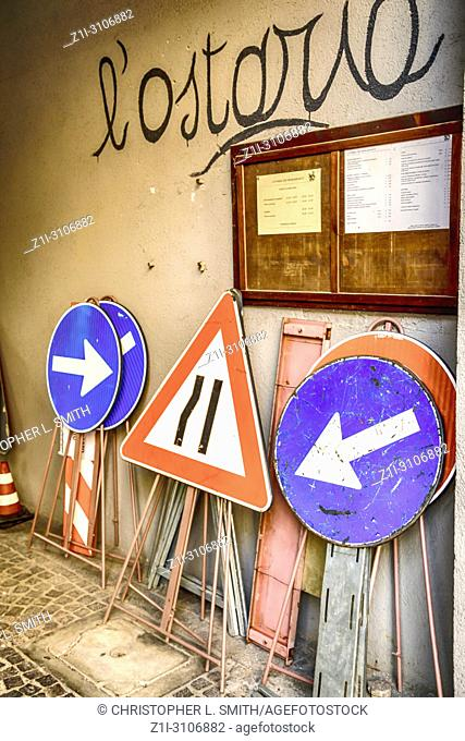 Group of portable road repair signs leant against a wall in Udine, Italy