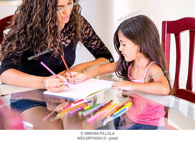 Teenage girl drawing with her little sister at table
