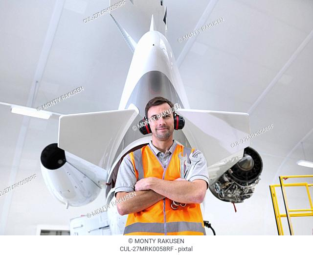Engineer standing with jet aircraft