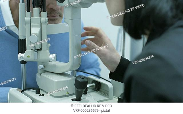 Male patient rests her head on the machine to be examined by the Female Optician