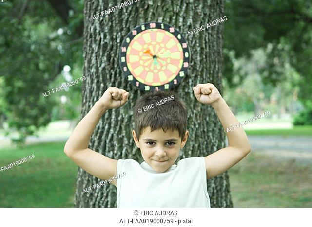 Boy standing in front of dart board on tree, arms up