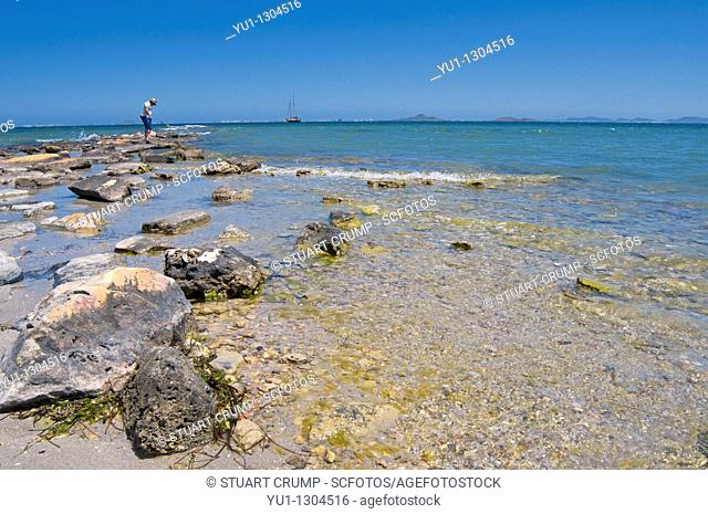 Man standing on rocks in the Mar Menor at Los Alcazares, Murcia, Spain