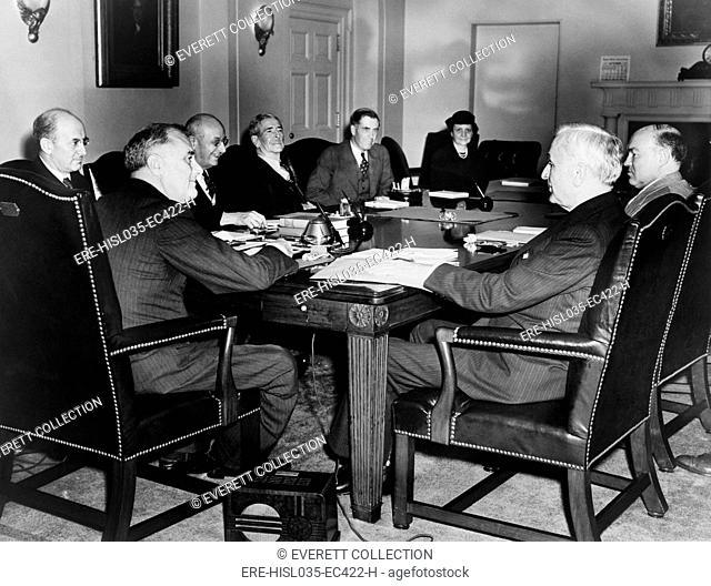 Pres. Franklin Roosevelt meets with cabinet in emergency session. 1938. Seated clockwise around a table: Franklin D. Roosevelt, Henry Morgenthau, Homer Cummings
