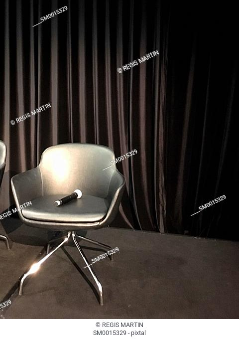 Microphone on a black armchair in front of a black curtain