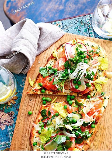 Salmon carpaccio and fennel pizza on serving board