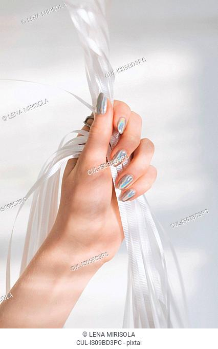 Cropped view of woman hand holding ribbons
