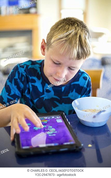 Avon, Outer Banks, North Carolina, USA. Pre-teenage American Boy Eating Breakfast while Playing on his Mobile Game Device