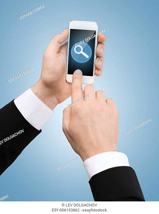 business, internet and technology concept - businessman touching screen of smartphone with magnifying glass