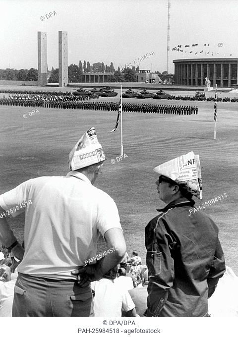 Two spectators have tinkered paper hats as sun protection, while they watch the parade of the British garrison of Berlin on the 13th of June in 1964 in honour...