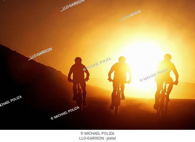 Silhouette of Three Cyclists at Sunset  Namib Desert, Namibia